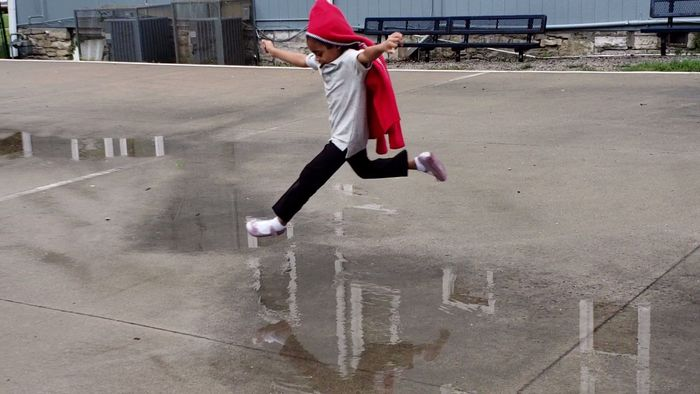 Girl jumping over puddle