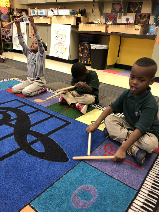Three TK students using their rhythm sticks to play along with Beethoven.